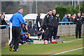 Dist:0.2km<br/>Managers and coaches stand in their respective technical areas beside the touchline at Wingate and Finchley football club.   The substitutes sit in their respective home and away dugouts, or keep warmed up by trotting up and down the touchline.