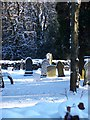 Sunlight and snow highlight the headstones in the churchyard at Holy Trinity Church, Lickey