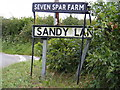 TM2557 : Sandy Lane & Seven Stars Farm signs by Adrian Cable