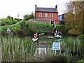 TF9340 : Scarecrows on pond, Wighton by John Brightley