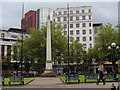 SP0686 : Monument and buildings by Birmingham Cathedral by Andrew Hill
