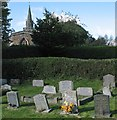 SK7510 : Burrough on the Hill: churchyard, east window and spire by John Sutton