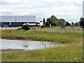 TQ4979 : Pond and Warehouse by Robin Webster