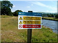 SN7027 : Warning notice on the bank of the Afon Sawdde near Llangadog by John Grayson