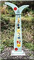 SJ9594 : Fossil tree signpost painted by Gerald England