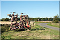 NZ0551 : Minor road with parked farm machinery by Trevor Littlewood