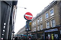 TQ3382 : View of stickers on a sign on the corner of Brick Lane and Sclater Street by Robert Lamb