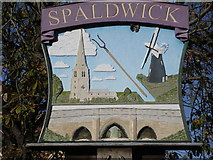 TL1272 : Village sign Spaldwick by Richard Greenwood