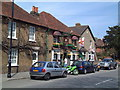 The pub has beautiful hanging baskets throughout the summer months. Adjacent are Wisteria Cottage and the Corner House, both listed buildings.