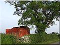 SJ6444 : Farm trailers beside a tree by Nigel Williams
