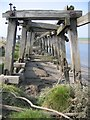Dist:0.5km<br/>A close up view of the jetty seen at [[387683]].  The method of construction can be seen, where massive nuts and bolts have been used, as well as the amount of rot in the remaining timbers.