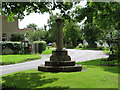 TL1070 : Cross and village green at Stow Longa by Steve F