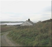 SH3368 : Ty'n Twll Cottage with Eglwys St Cwyfan Church in the background by Eric Jones