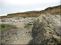 SH3368 : Pre-Cambrian rocks exposed by the retreat of the boulder clay cliffs at Porth Cwyfan by Eric Jones
