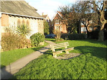 TQ0202 : Seat in the churchyard of St James the Great, East Ham Road by Basher Eyre