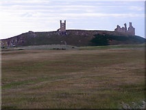 NU2422 : Expansive grassy meadow with Dunstanburgh Castle ruins in distance by C Michael Hogan