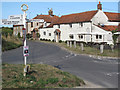 TG0442 : The Wiveton Bell pub and signpost by Andy Parrett
