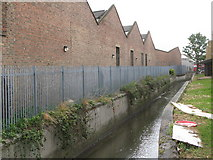 TQ3772 : The River Ravensbourne at the rear of Catford bus garage, Bromley Road, SE6 by Mike Quinn