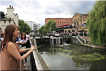 TQ2884 : Tourists watching Camden lock in operation by Roger Davies