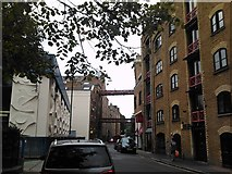 TQ3480 : View of the footbridges linking the former warehouses crossing Wapping High Street by Robert Lamb