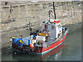NU2520 : Fishing boat moored in Craster Harbour by Graham Robson
