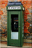 R4560 : Bunratty - green Telefon booth against grey stone and red brick building by Joseph Mischyshyn