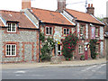 TF9441 : Brick and flint pub and cottages by Pauline E