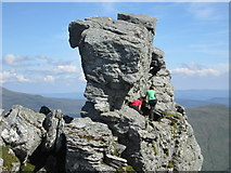 """NN2605 : Two people climbing the rocky outcrop of """"The Cobbler� by Peter S"""