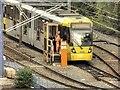 SJ8499 : Metrolink Tram Waiting Outside Victoria Station by David Dixon