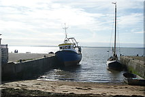 TQ8485 : View of a boat moored up at a jetty next to the beach by Robert Lamb