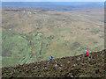 NR9735 : Mountain walkers descending heather slope by Trevor Littlewood