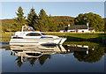 NH3303 : Boat passing bridge keeper's cottage, Aberchalder by Craig Wallace