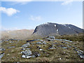 NN1373 : Rocks and grass near summit of Meall an t-Suidhe by Trevor Littlewood