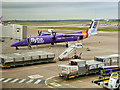 SJ8284 : Flybe Aircraft Being Services at Manchester Airport by David Dixon