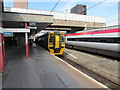 SO9198 : Diesel train and electric train in Wolverhampton railway station by Jaggery