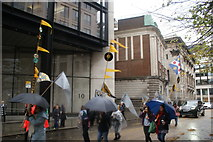 TQ3281 : View of flags and vinyls on poles in the Lord Mayor's Parade from Gresham Street by Robert Lamb