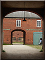 SK3622 : Calke Abbey - stables through the arches by Chris Allen
