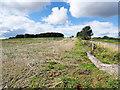 NZ3131 : Stubble field near crossroads by Trevor Littlewood
