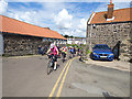 NU2519 : Cyclists through Craster by Stephen Craven