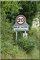 TF7715 : West Acre Village name sign on Greenhill Road by Adrian Cable