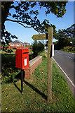TA3624 : Post box & fingerpost on Withernsea Road at Nevills Bridge by Ian S