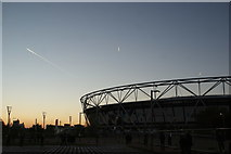 TQ3783 : View of airplane vapour trails above the London Stadium from the South Lawn of the Olympic Park by Robert Lamb