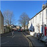 TL4658 : Hooper Street: bright sky, bright doors and a cyclist by John Sutton