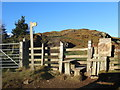 SJ1367 : Stile and signpost, Penycloddiau by Eirian Evans
