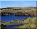 SN8988 : Lane with cattle grid and view of Clywedog Reservoir by Andrew Hill