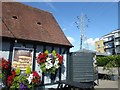 TQ4674 : Hanging baskets and a pylon by Marathon