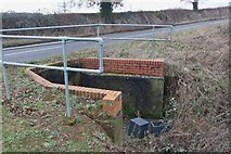 SP7735 : Drainage channel going under Stratford Road, Beachampton by David Howard