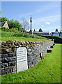 NY7146 : Retaining wall with inset milestone by Trevor Littlewood