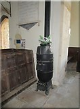 SP9599 : Church of St. John the Baptist, Wakerley, cast iron stove by Jonathan Thacker