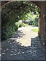 TF8342 : Garden through an arch in Burnham Market by Richard Humphrey